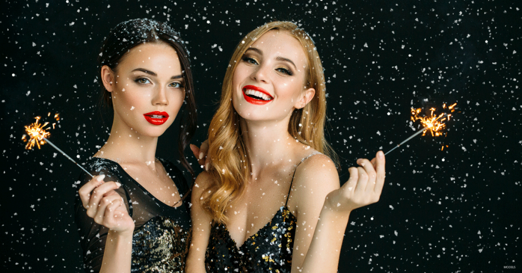 Two young women wearing bright red lipstick holding sparklers