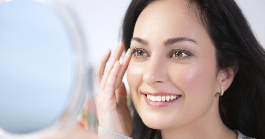 portrait of woman admiring skin in mirror
